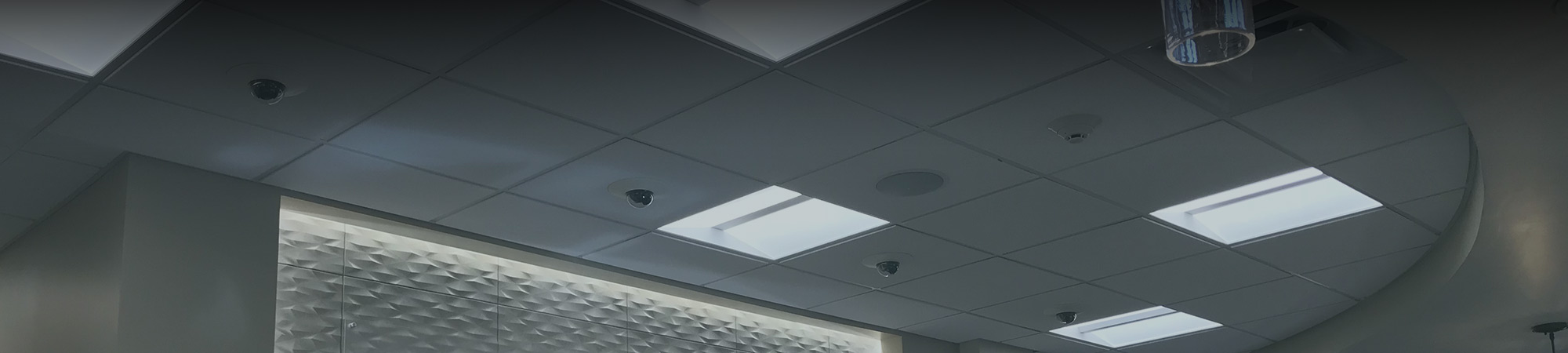Commercial acoustical tile ceiling with integrated security cameras, lights, sprinkler heads, and speakers in a medical facility